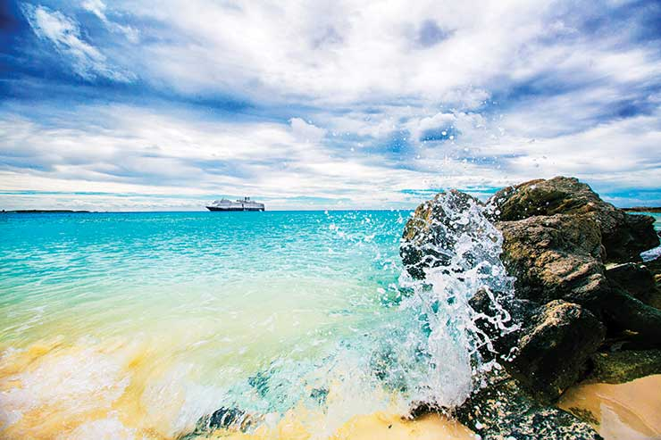 Caribbean cruise waves crashing a rock on the beach iStock_77635807