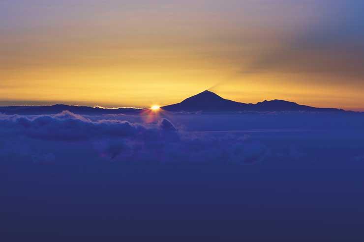 Sunset over mountain and cloud horizon