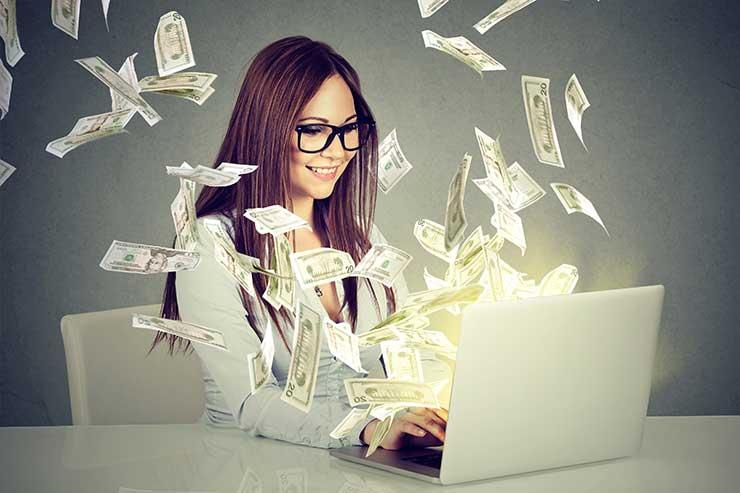 Woman with laptop surrounded by money