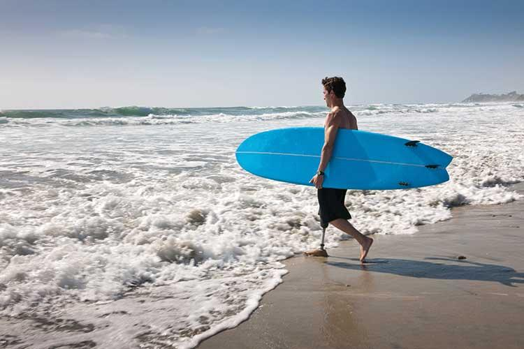 Man with surfboard entering sea
