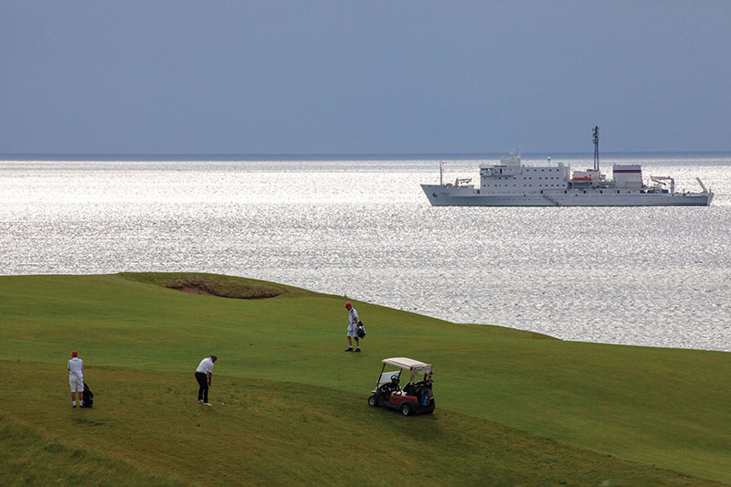 Playing golf on Cabot Links, Nova Scotia, with Akademik Ioffe in the background © Peter Ellegard-934