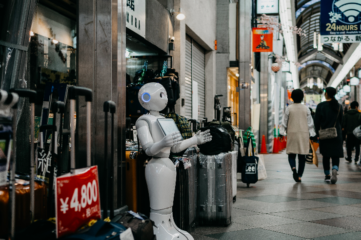 Robot standing by luggage_Photo by Lukas on Unsplash.png