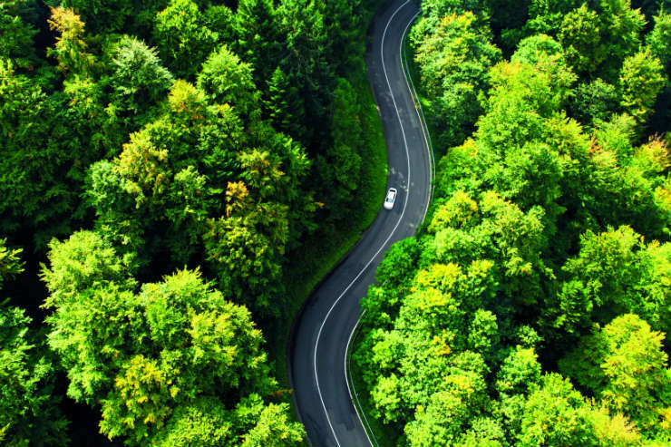 Aerial shot of car driving along winding country road