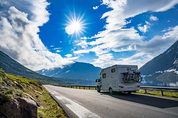 Motorhome driving by fjord in European alps