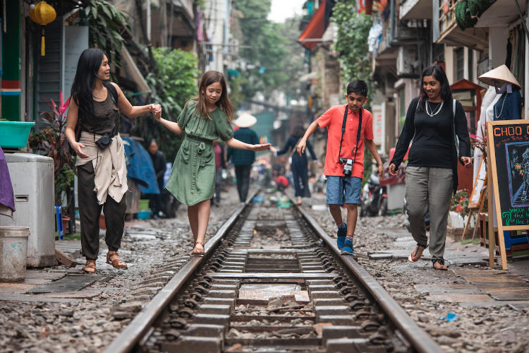 G Adventures National Geographic Vietnam Hanoi Train Street Mothers Children Walking.jpg